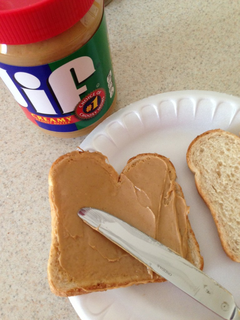 overhead view of jar of JIF peanut butter and peanut butter being spread on bread using a knife