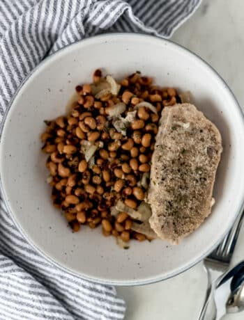 large bowl of slow cooker black eyed peas with a single pork chop next to a napkin