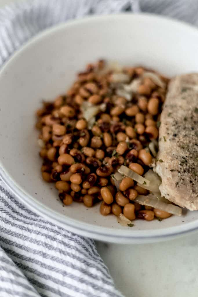 close up side view bowl of slow cooker black eyed peas and pork chop