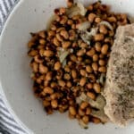 bowl with black eyed peas, onion, and a piece of pork chop