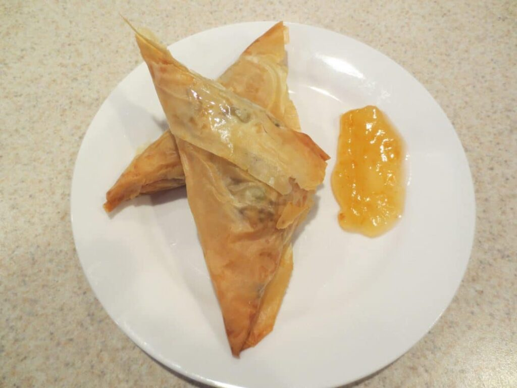 Ground Beef Samosas are a baked triangular shaped pastry that is savory and loaded with flavor. They can be served hot or cold as a snack or main dish. simplylakita.com #samosas