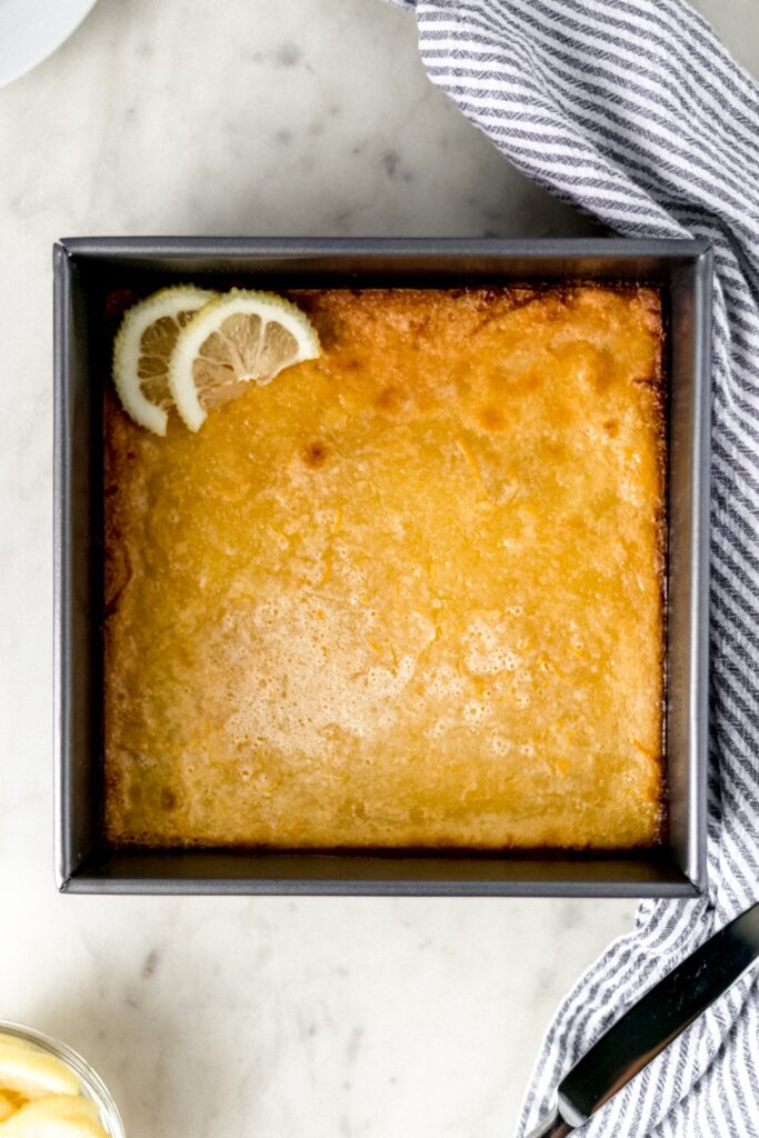overhead view original lemon bars in a baking dish with napkin, knife, and lemon slices