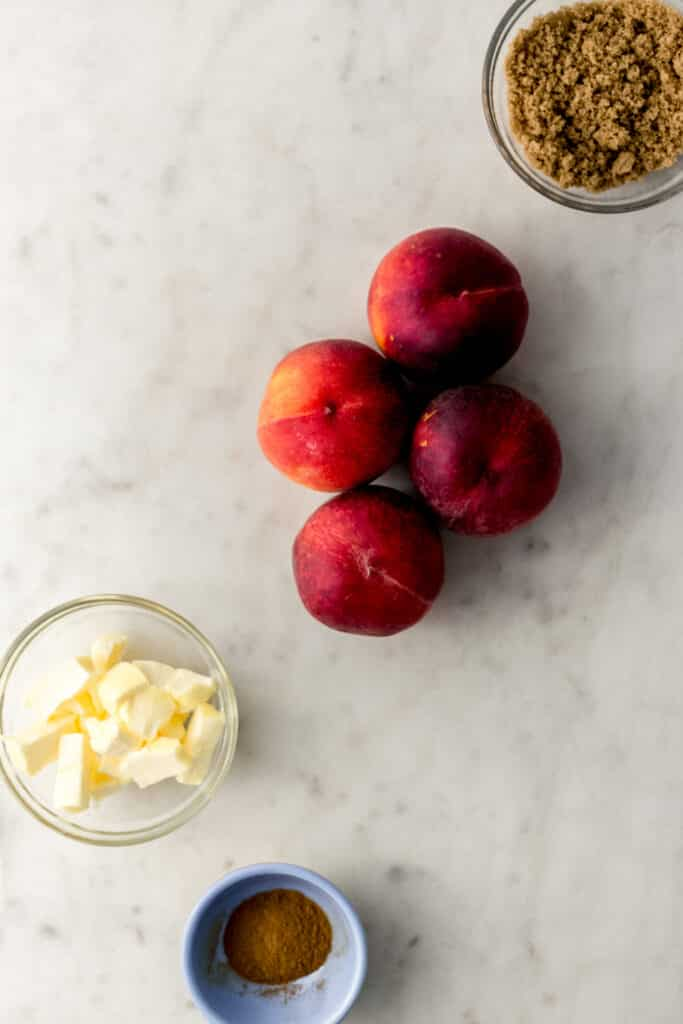 ingredients for brown sugar peaches in small bowls with 4 fresh peaches