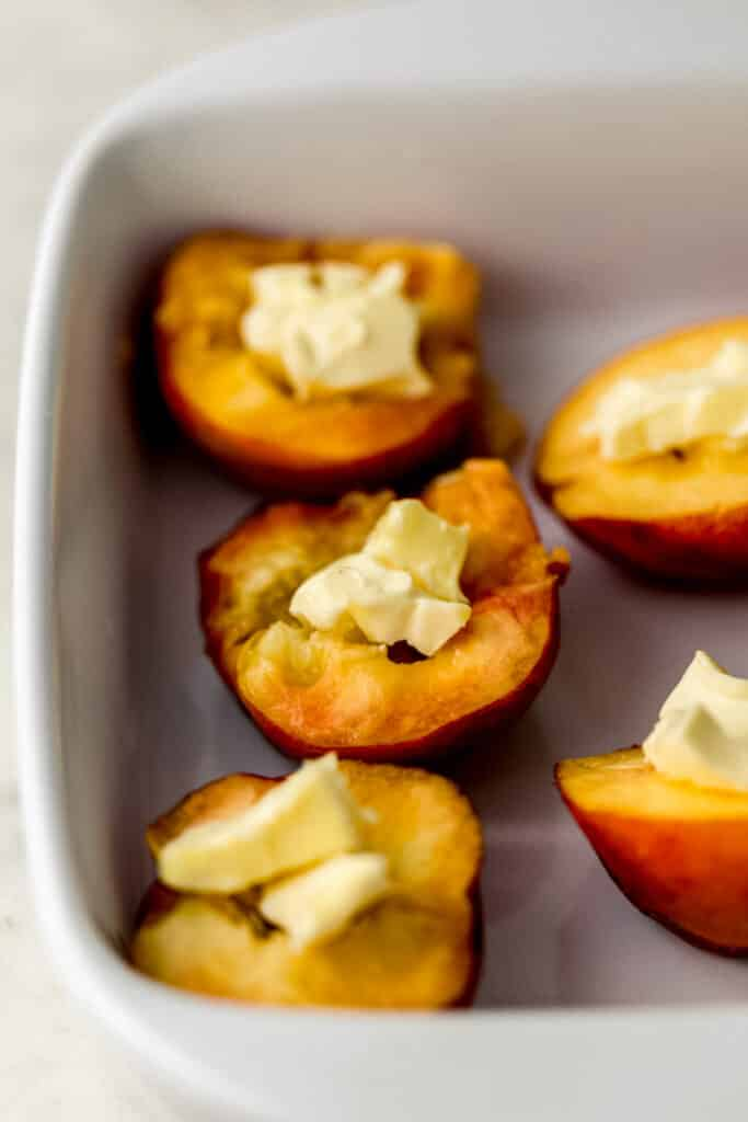 close up side view peaches cut in half with topped with butter in white baking dish