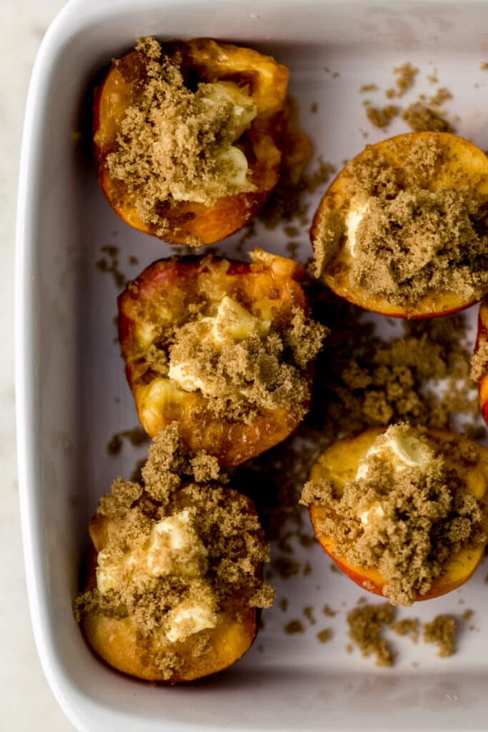 peaches in white baking dish cut in half topped with butter and brown sugar