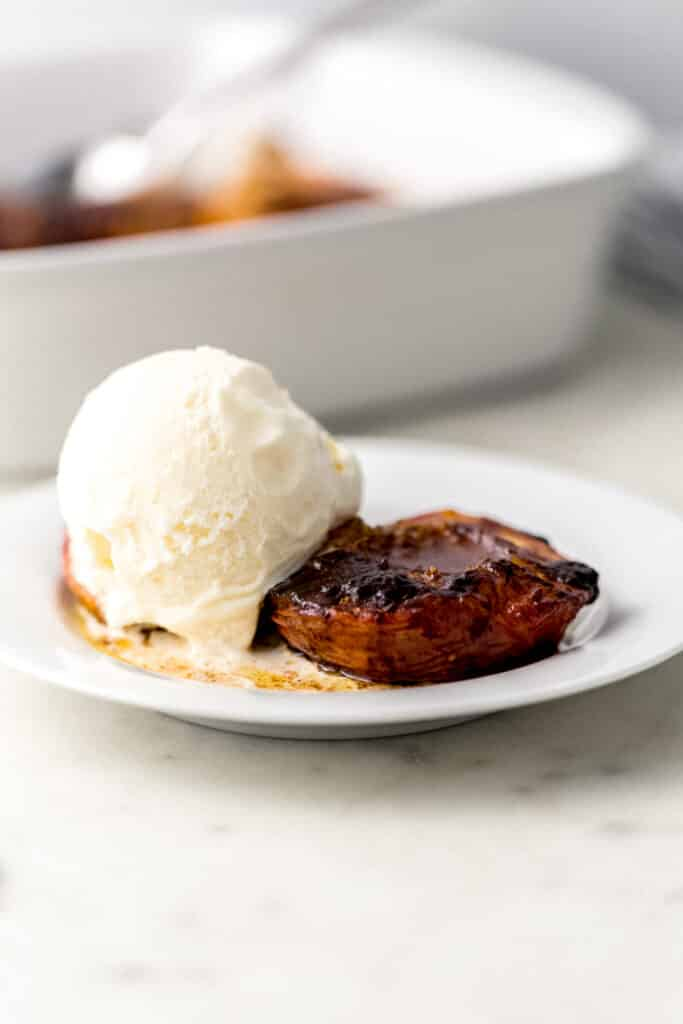 small white plate with 2 baked peaches on it with a scoop of vanilla ice cream