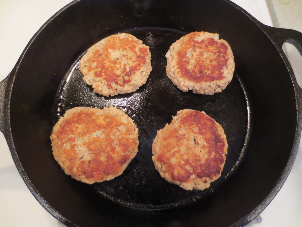 four salmon patties cooking in a cast iron skillet