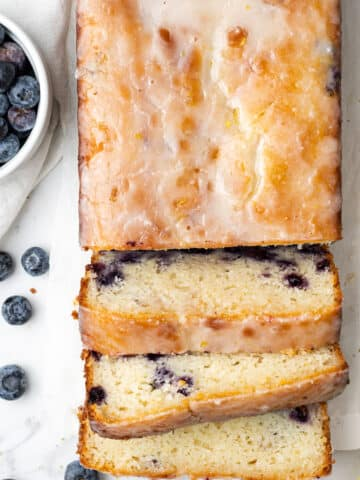overhead view lemon blueberry bread cut into slices next to a small white bowl of fresh blueberries