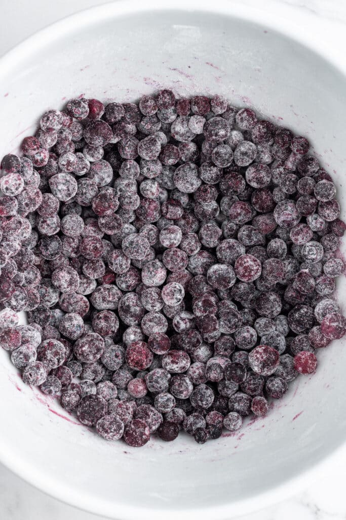 blueberries and flour combined in mixing bowl