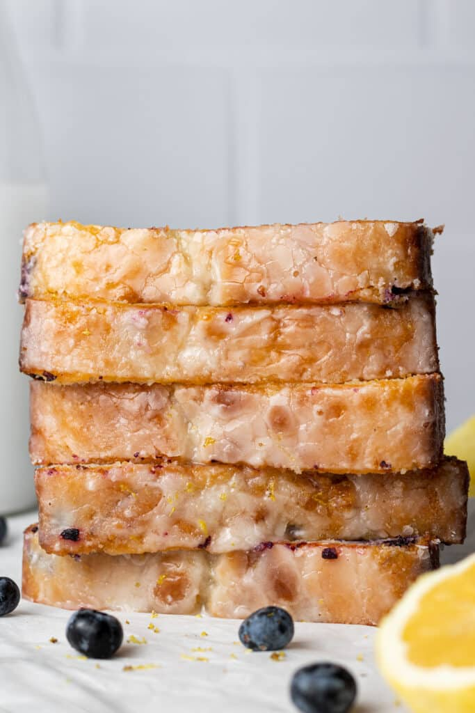 side view slices of lemon bread stacked on top of each other with lemon wedges