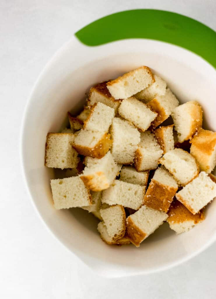 butter pound cake cut up in white medium mixing bowl