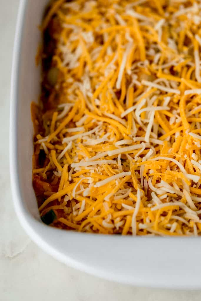 chicken enchilada pasta topped with shredded cheese in white baking dish