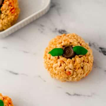 pumpkin shaped rice krispie treats on marble surface