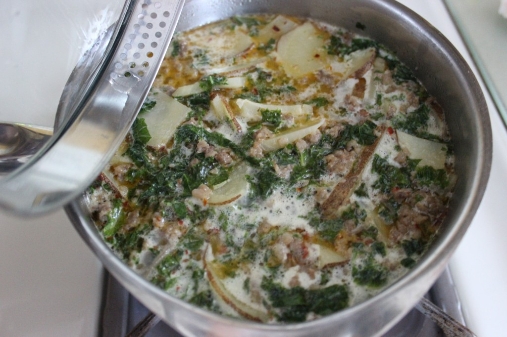 Finished potato kale and sausage soup in saucepan on stove