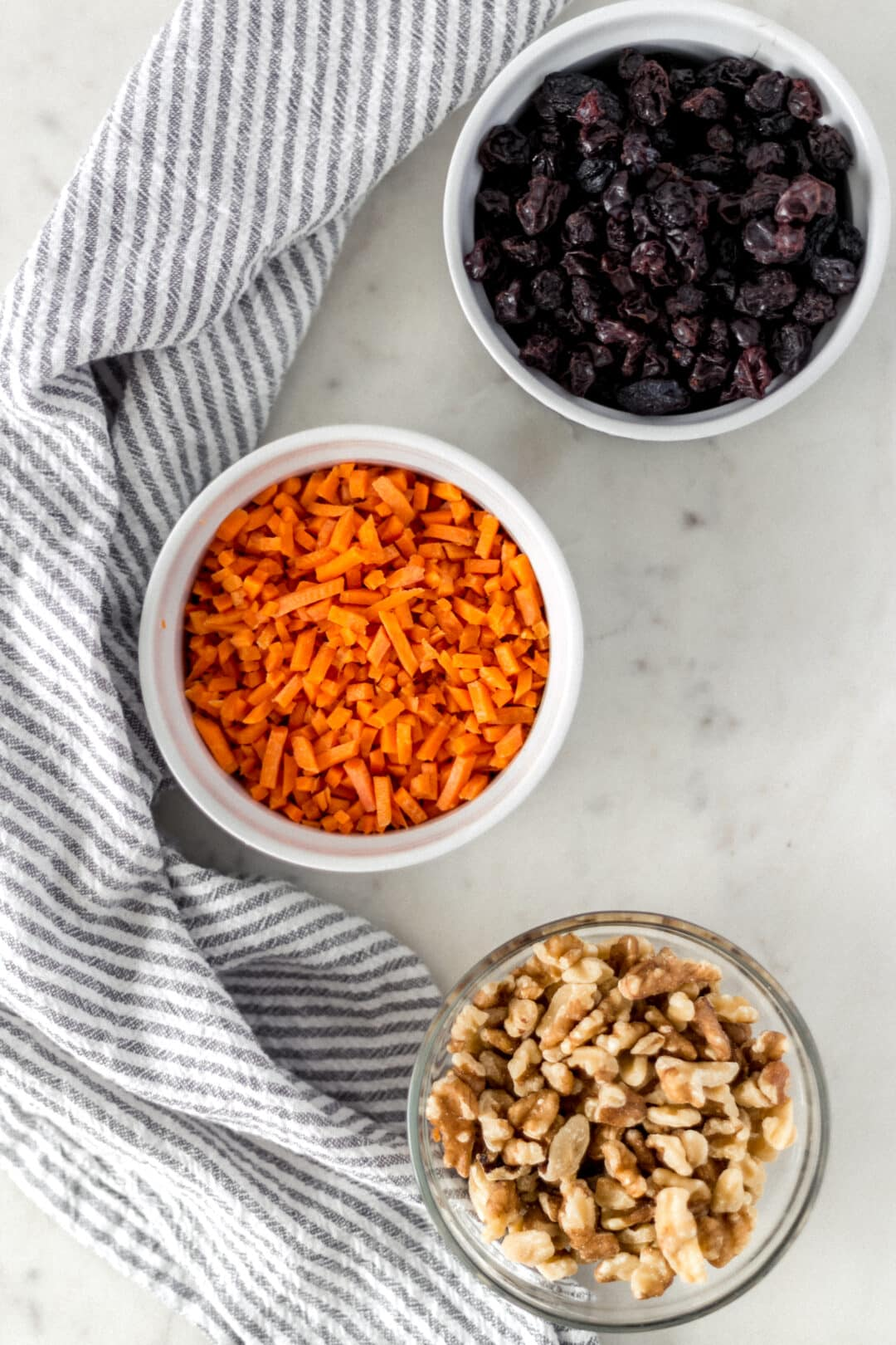 small bowls with shredded carrot, walnuts, and raisins