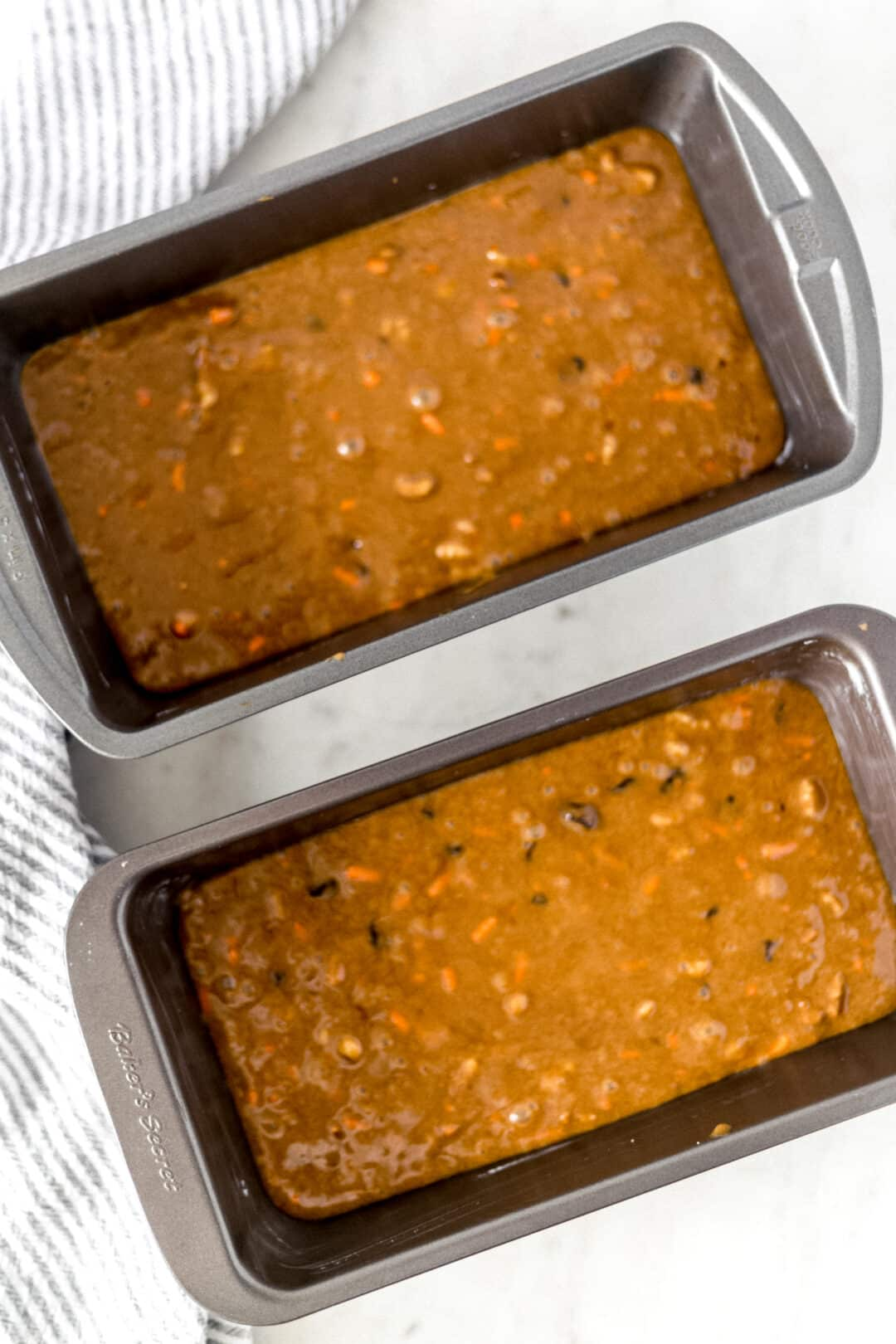 uncooked carrot raisin bread poured into two loaf pans for baking