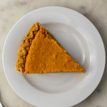 overhead view slice of sweet potato pie on white plate next to fork.