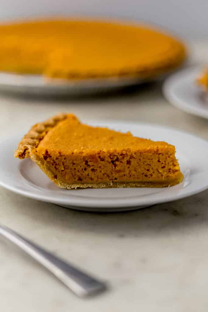 close up side view slice sweet potato pie on white plate