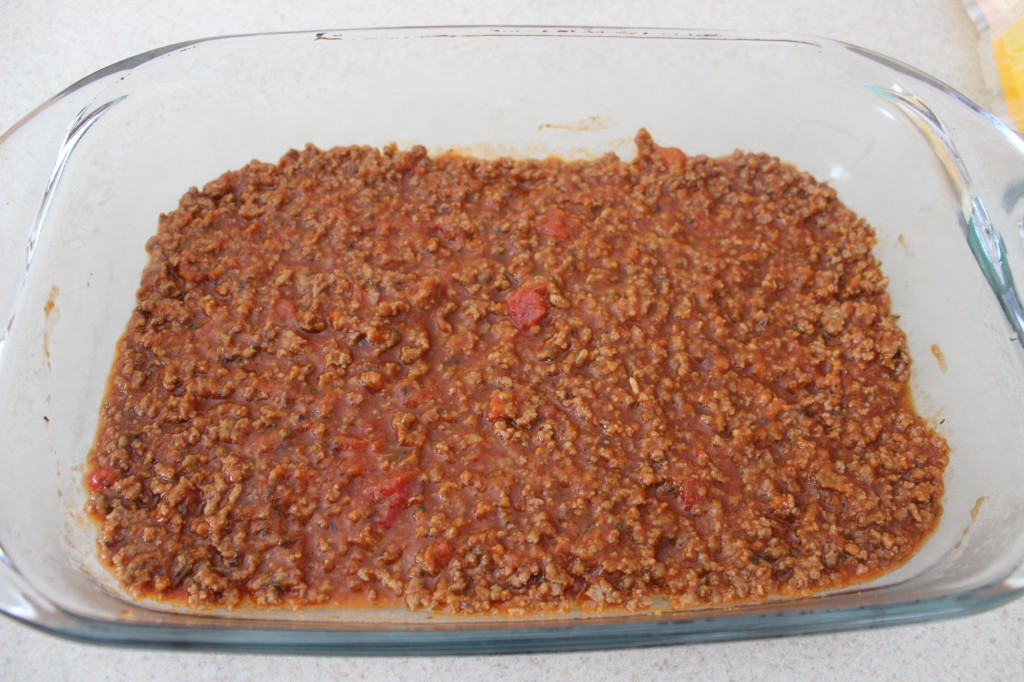 meat sauce at the bottom of a glass baking dish