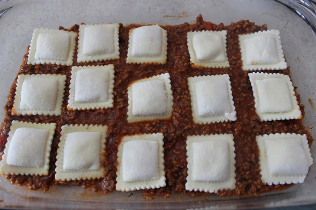 frozen cheese ravioli on top of meat sauce in glass baking dish