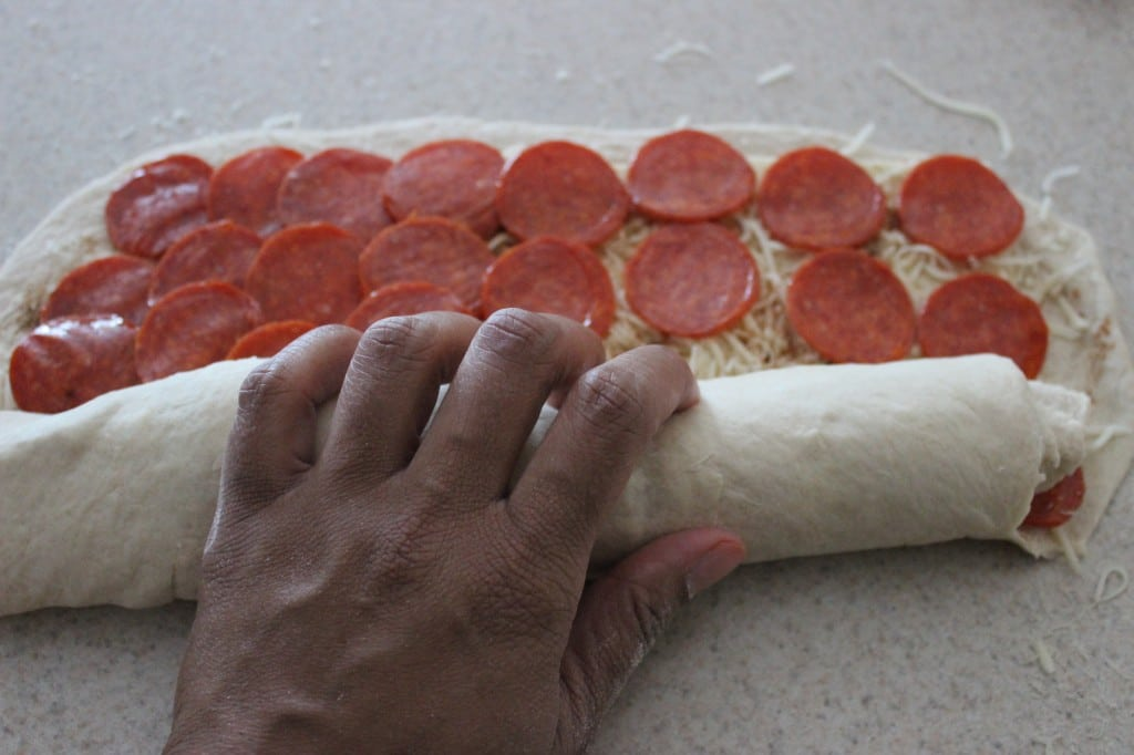 hand rolling pizza dough for pepperoni bread