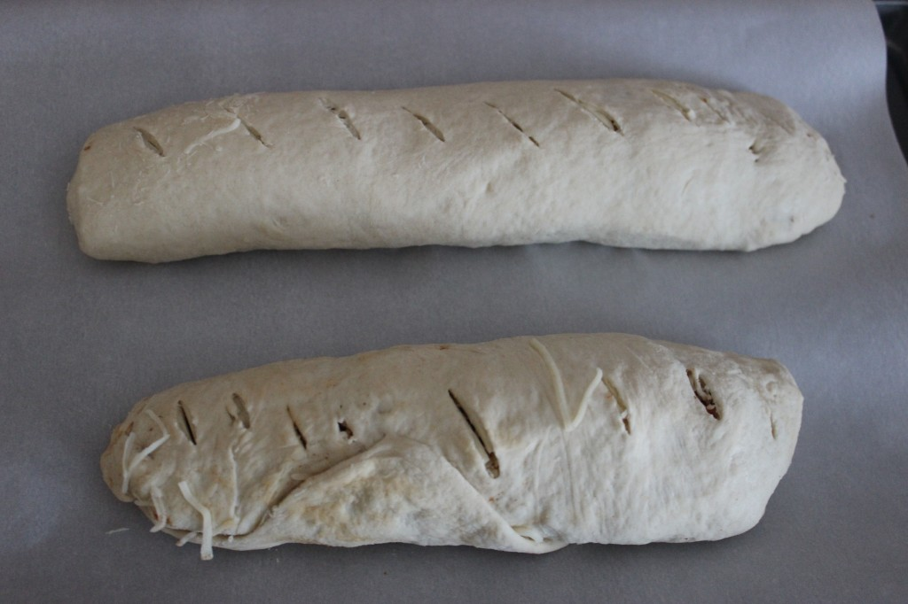rolled pepperoni bread on parchment lined baking sheet before baking
