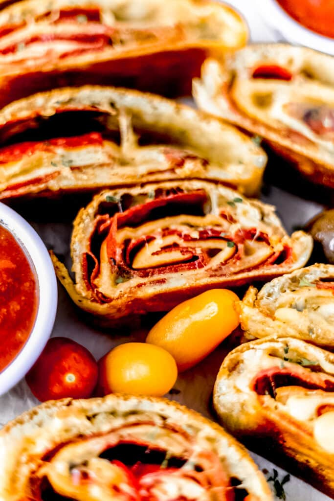 close up side view pepperoni bread next to sauce in small bowl