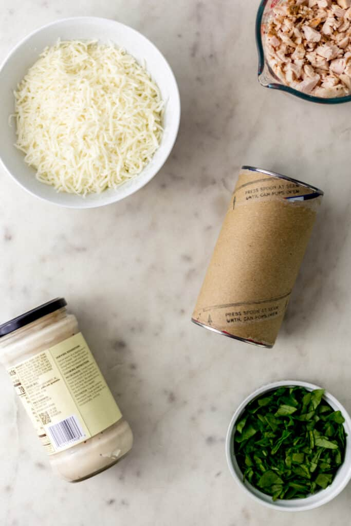 ingredients needed for alfredo biscuit pizzas on marble