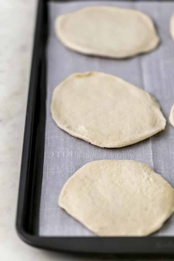 biscuit dough flattened on parchment lined baking sheet