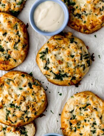 mini chicken alfredo biscuit pizzas on parchment with dipping sauce in small blue bowl