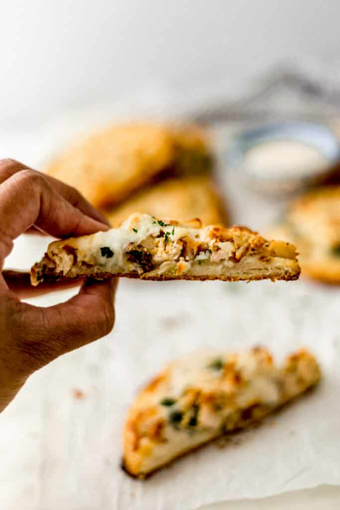 hand holding half of alfredo biscuit pizza