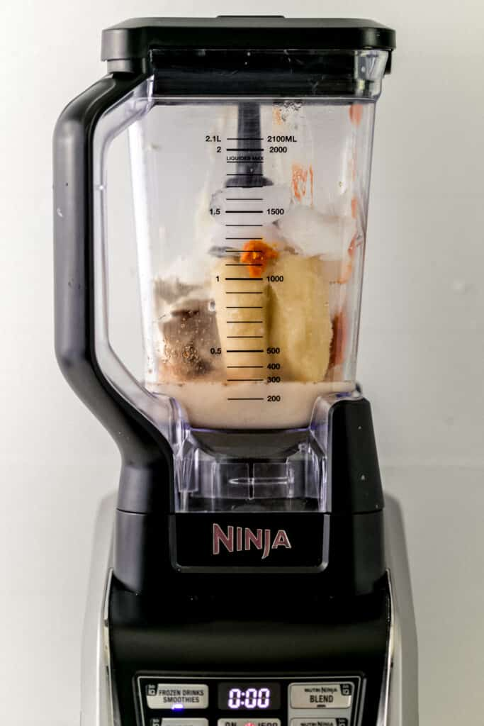 ingredients for pumpkin spice smoothie added into a blender.