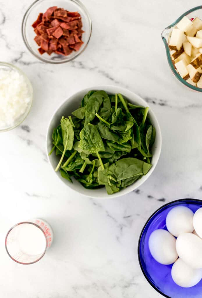 overhead view of ingredients needed to make frittata in separate containers on marble surface