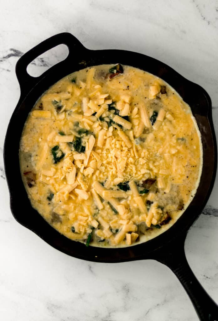 ingredients to make frittata mixed together in cast iron skillet