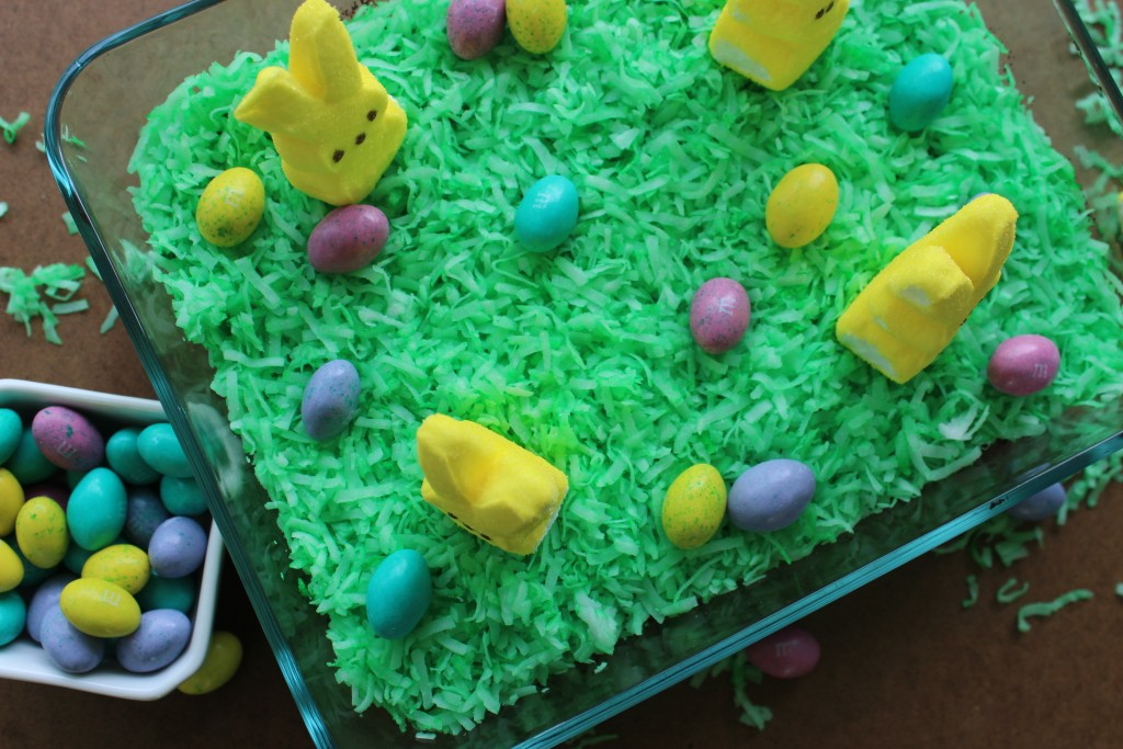 overhead shot of oreo dirt pudding with green colored coconut as grass, marshmallow peeps, and candy