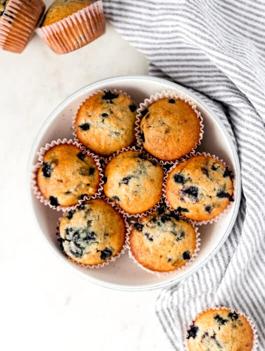 batch of blueberry muffins in a large bowl over a napkin