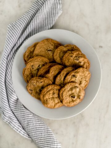 batch of chocolate chip cookies on white dinner plate with cloth napkin