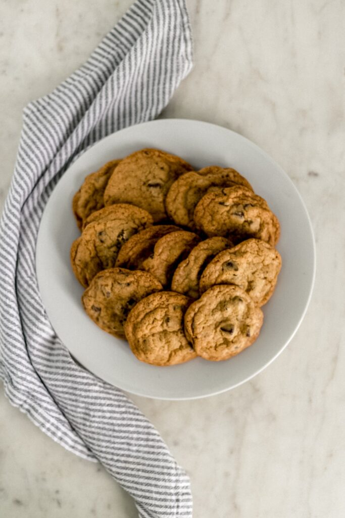 baked chocolate chip cookies on white dinner plate with cloth napkin