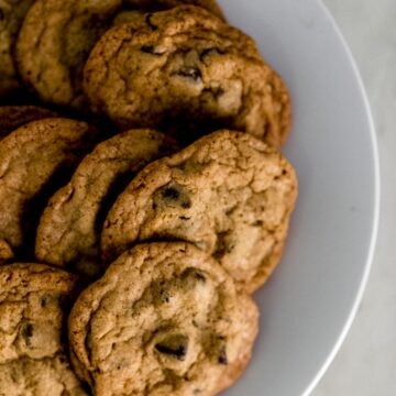 white plate with a batch of chocolate chip cookies on it