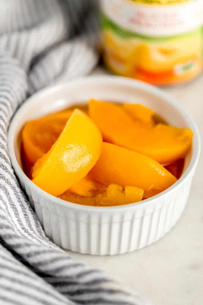 small white bowl with sliced peaches in it next to cloth napkin