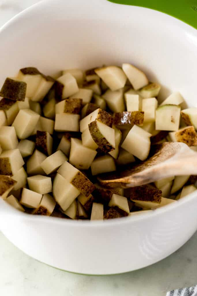 diced potatoes in a large white mixing bowl with wooden spoon