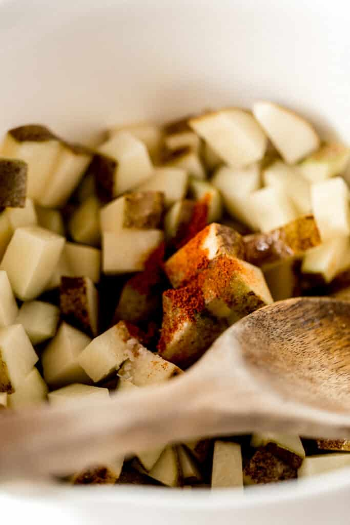 roasted potatoes in large white bowl topped with seasoning