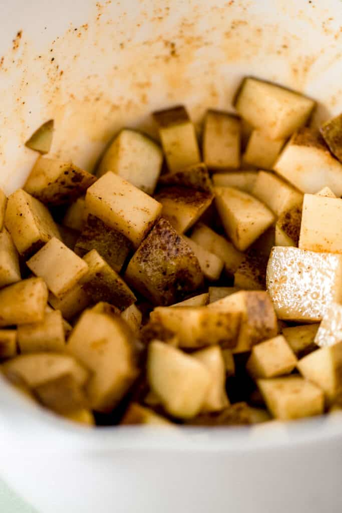 potatoes in large mixing bowl tossed in olive oil and seasonings
