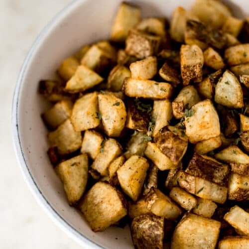 close up side view easy roasted potatoes in large white bowl