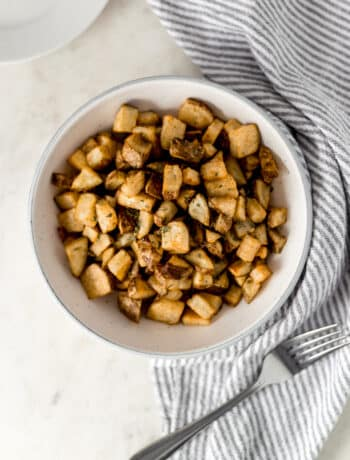overhead view easy roasted potatoes in large white serving bowl with fork, plate, and napkin