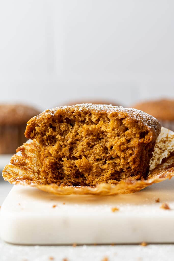 close up side view single gingerbread muffin cut in half on muffin liner