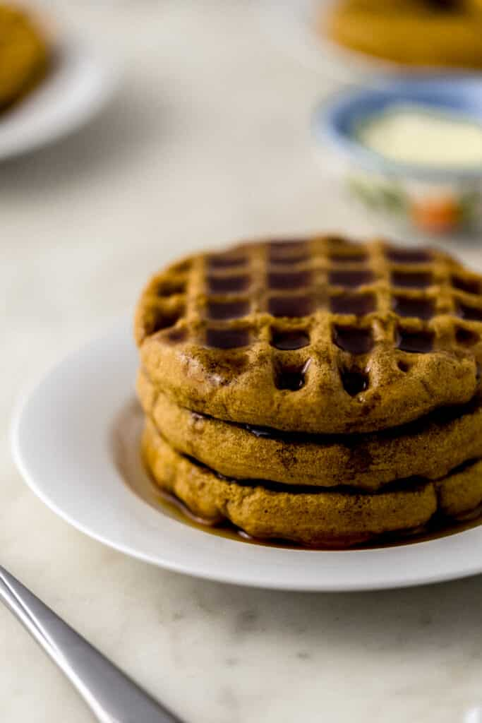 three waffles stacked on white plate topped with maple syrup.