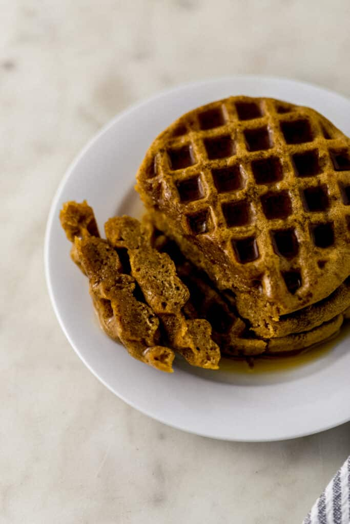 waffles stacked on a white plate topped with maple syrup.