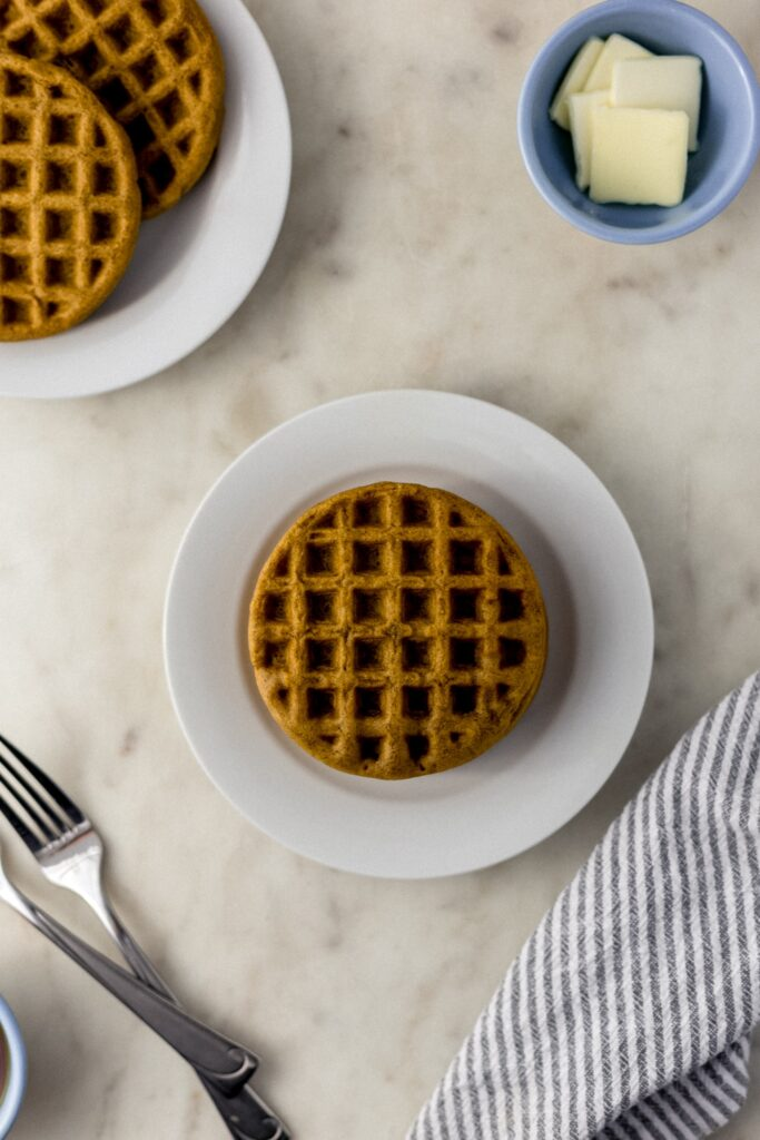 waffles on a small white plate with forks, cloth napkin, and small bowl with butter.