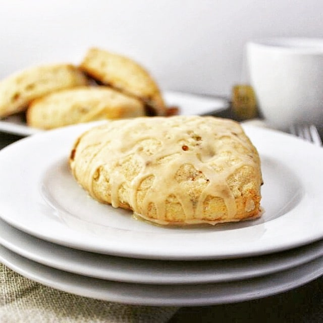 maple pecan scone on top of a stack of three white plates